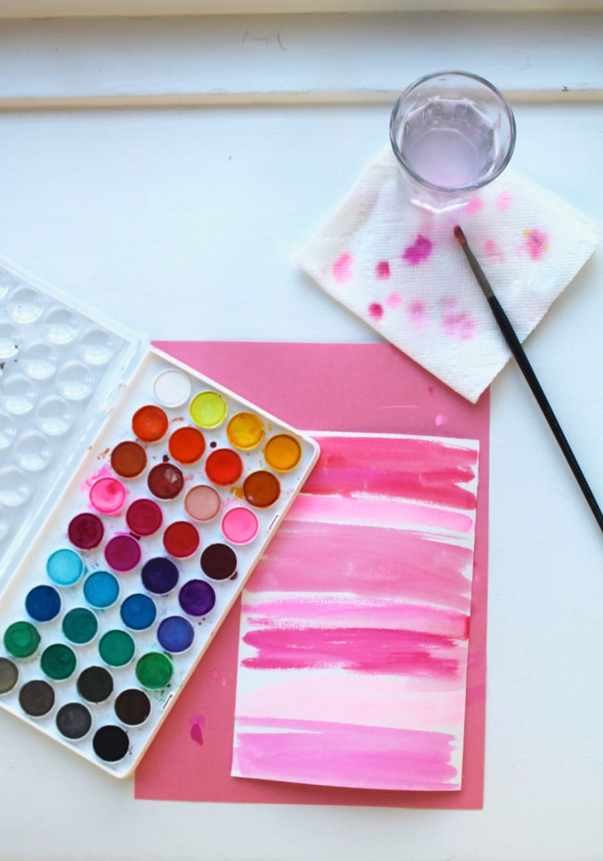 art supplies, watercolors, paint briush, paper with stripes in shades of pink