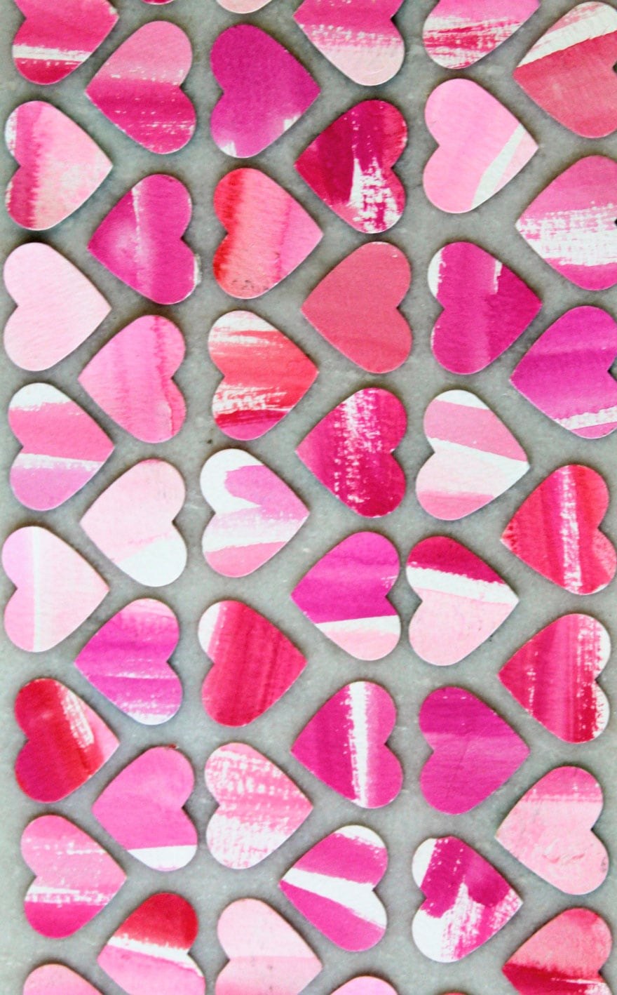 pink, red, white patterns on miniature heart cutouts on marble background