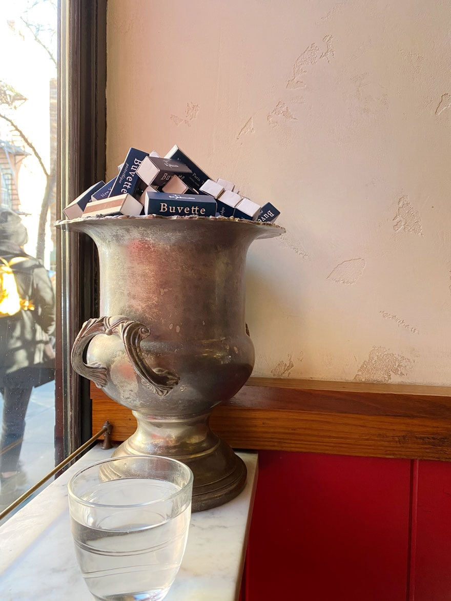 a tarnished silver champagne bucket with matchbooks on marble counter