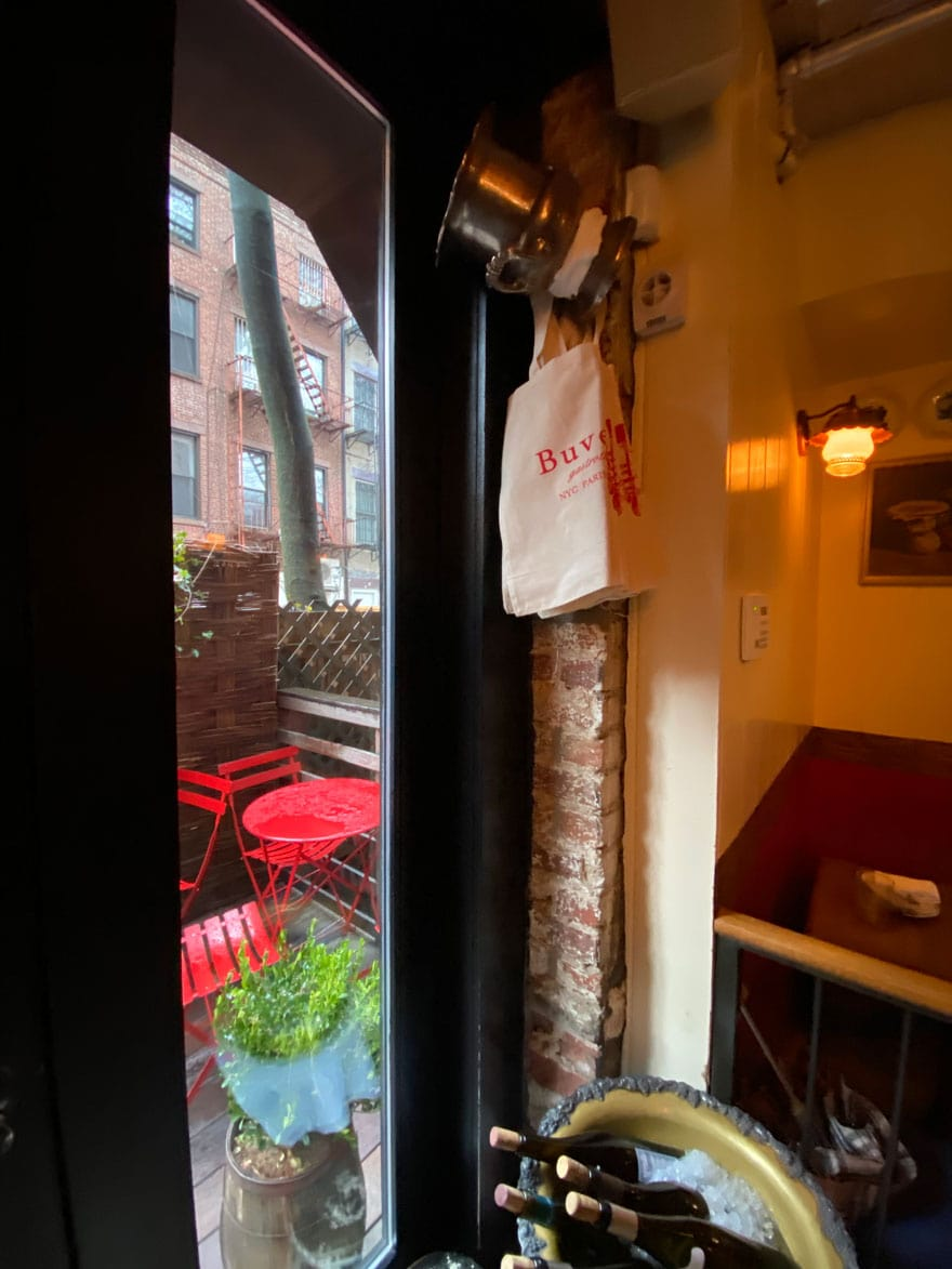 view of patio with red cafe tables and tote bags on hook