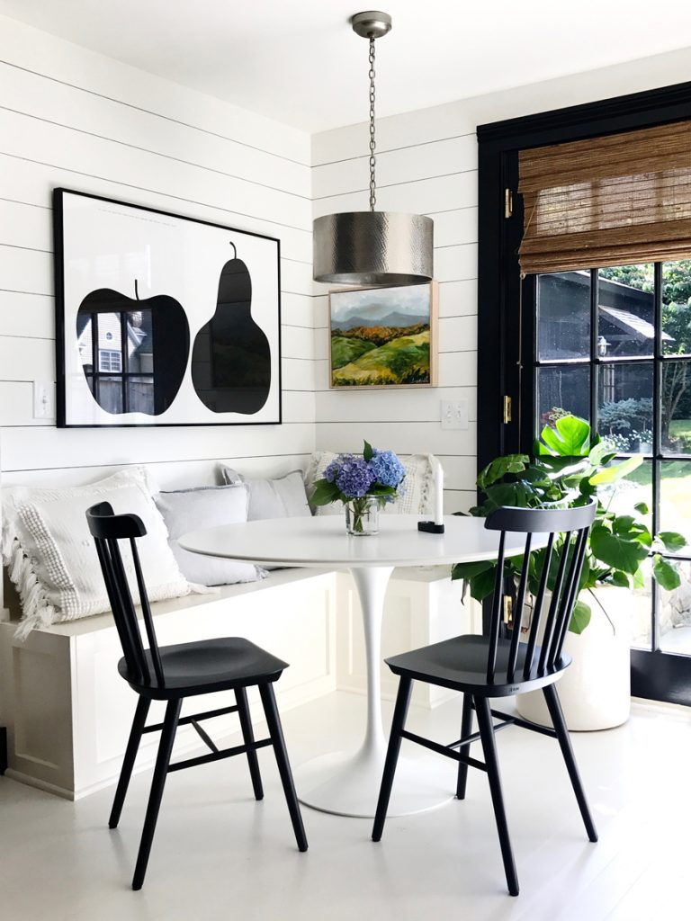 round table with black chairs and built-in bench with Enzo Mari poster