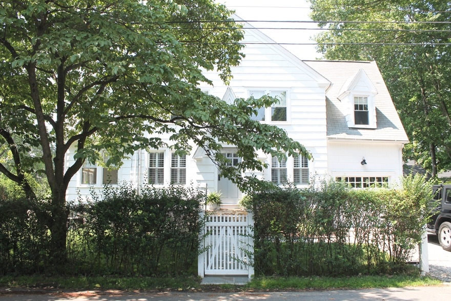 A New England Beach Cottage with hedges and picket Fence