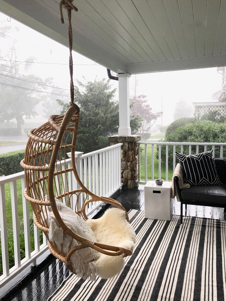 rattan hanging chair on porch with black and white striped rug