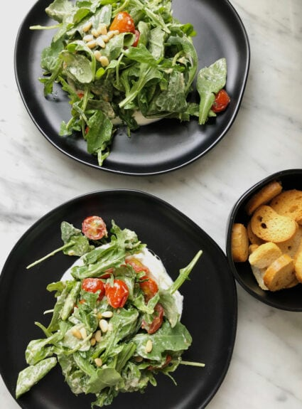 salad on black plates with small black bowl of tiny toasts