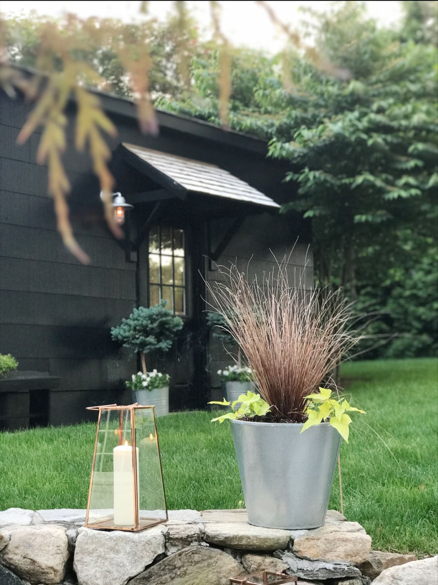 black garage with portico and plants plus a lantern with a candle
