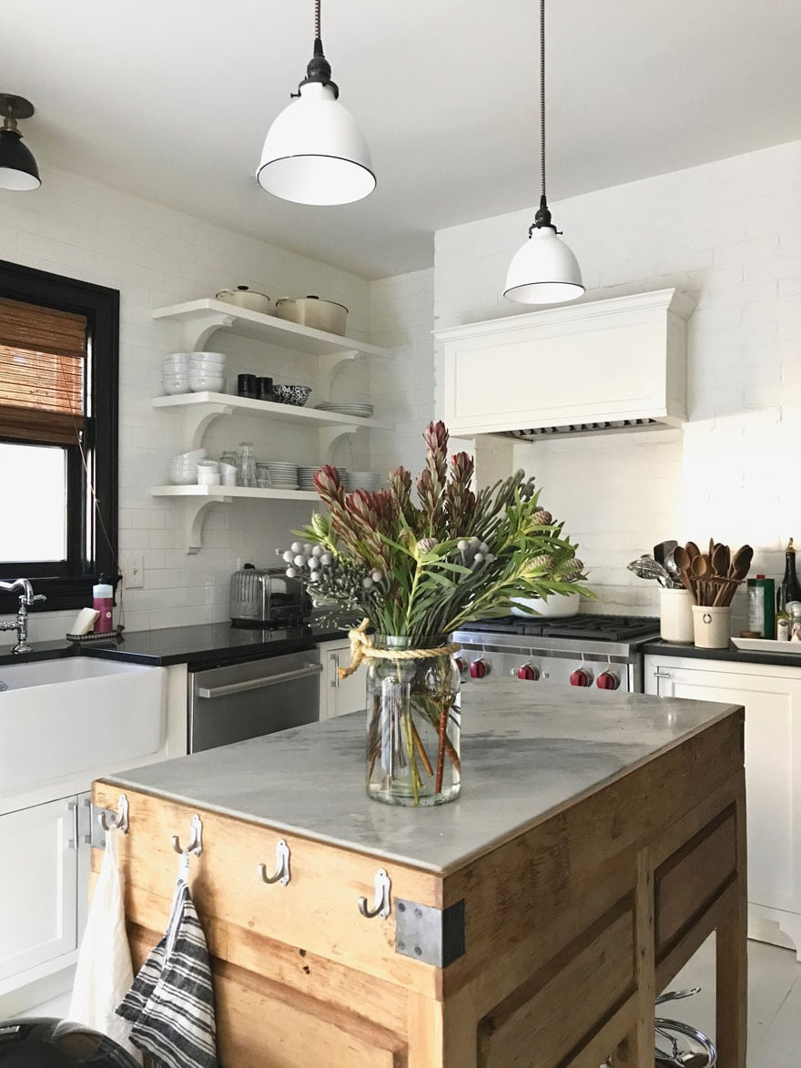 rustic kitchen island in kitchen with farm sink and open shelves