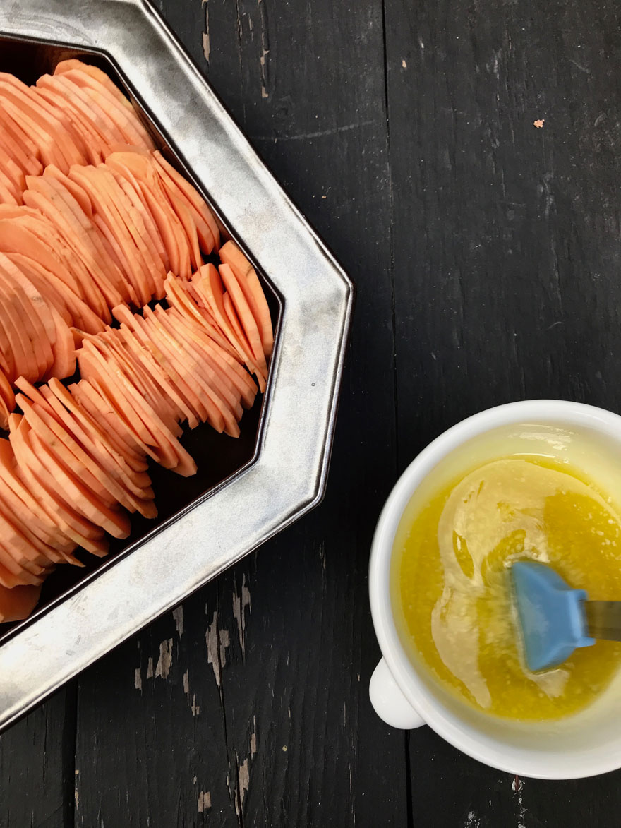 Arrange sweet potatoes and brush with butter and olive oil