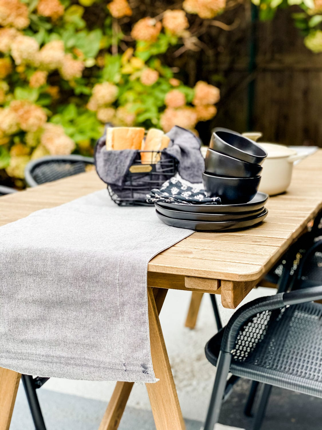 an outdoor table with black dishes and basket of bread with hydrangeas in background