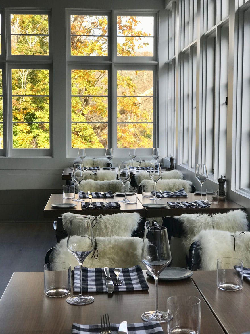 The dining room at GrayBarns Tavern overlooking the Silvermine River. Each chair has a sheepskin tied with a piece of leather to hold it in place.