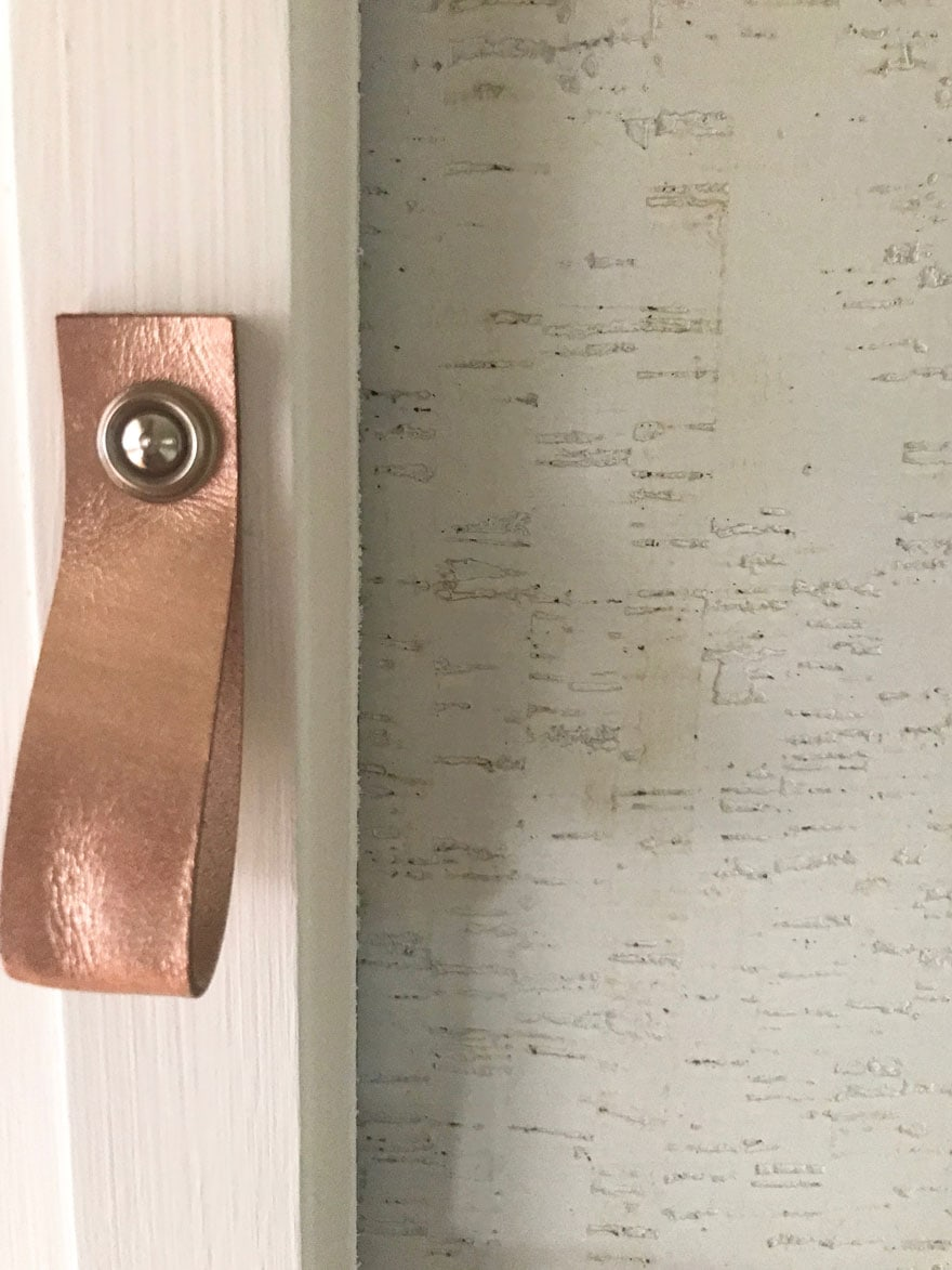 leather pulls in rose gold and wallpaper covering glass in an ikea armoire updates it with Chalk Paint by Annie Sloan