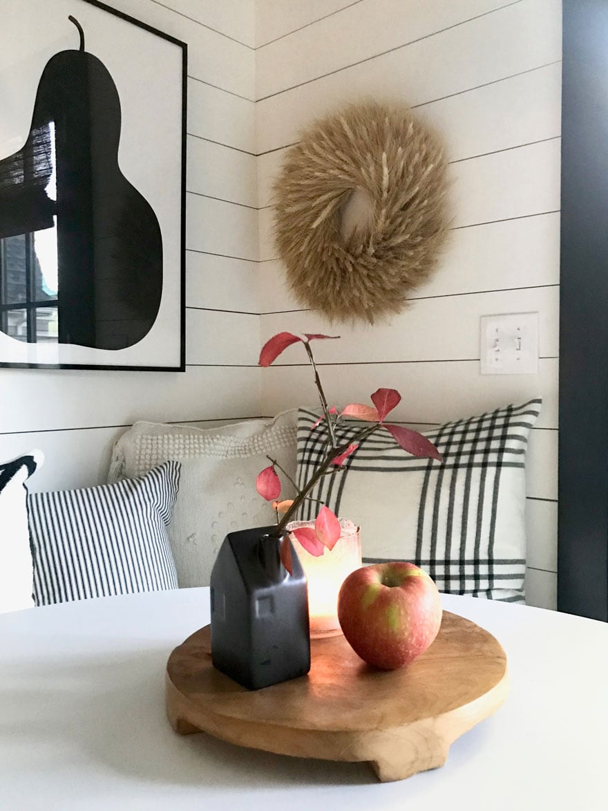 A round wood board with a few items warms up a white table in the kitchen
