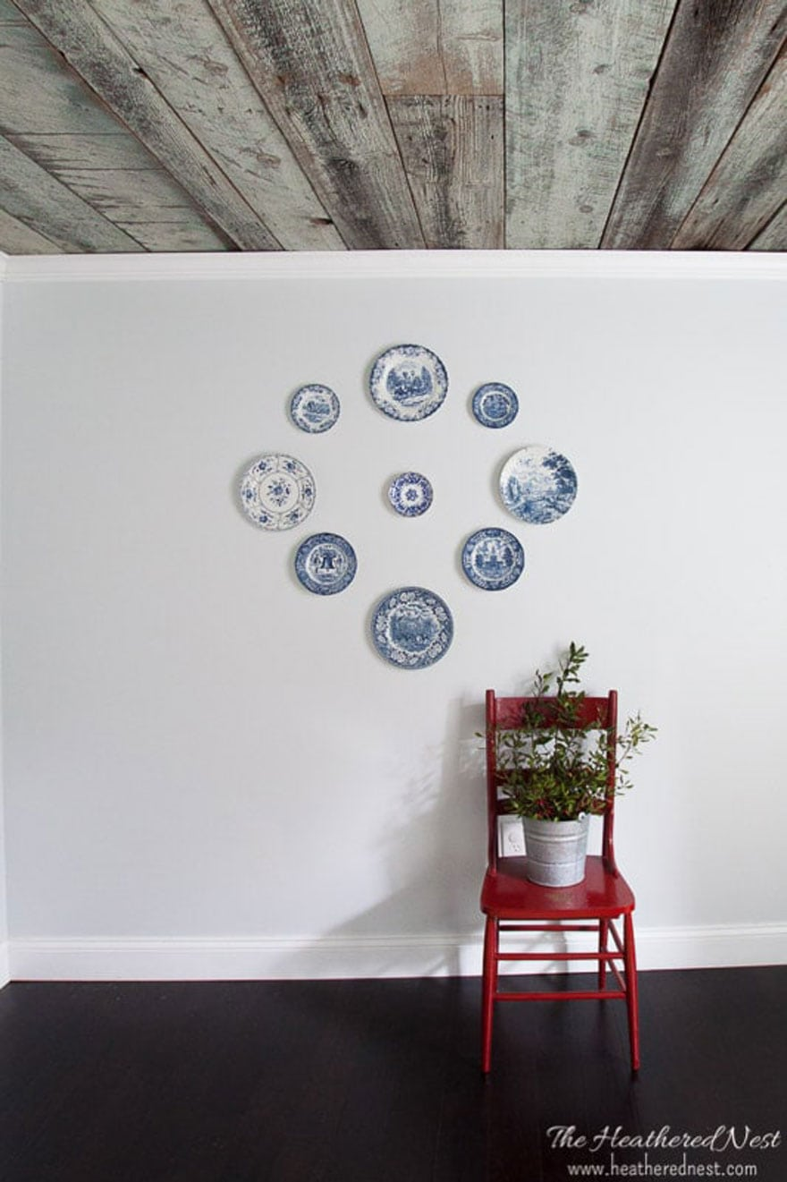 A holiday display with blue and white plates and a red chair with a bucket of fresh greens