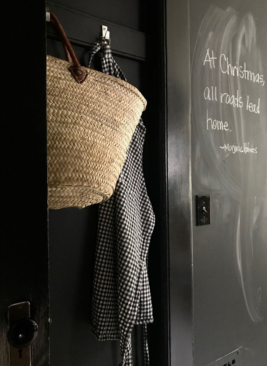 A small space between out entry and the kitchen holds aprons and market bags next to our large chalkboard wall with a Christmas quote