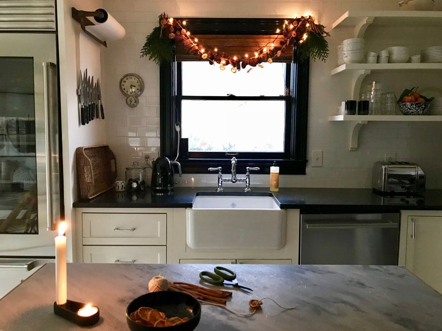 pinecone and citrus garland over the kitchen window with twinkle lights at a Christmas touch