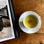 cup with gold drink on wood table with book page open