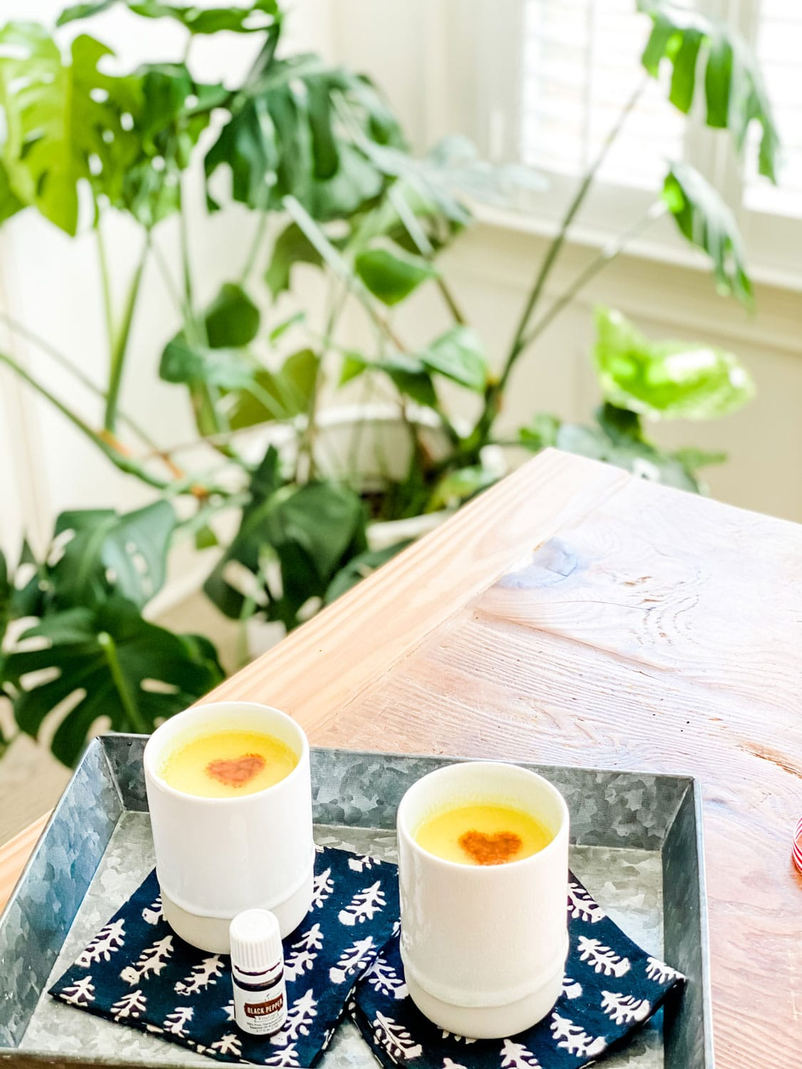 golden milk with turmeric heart on black napkins with plants
