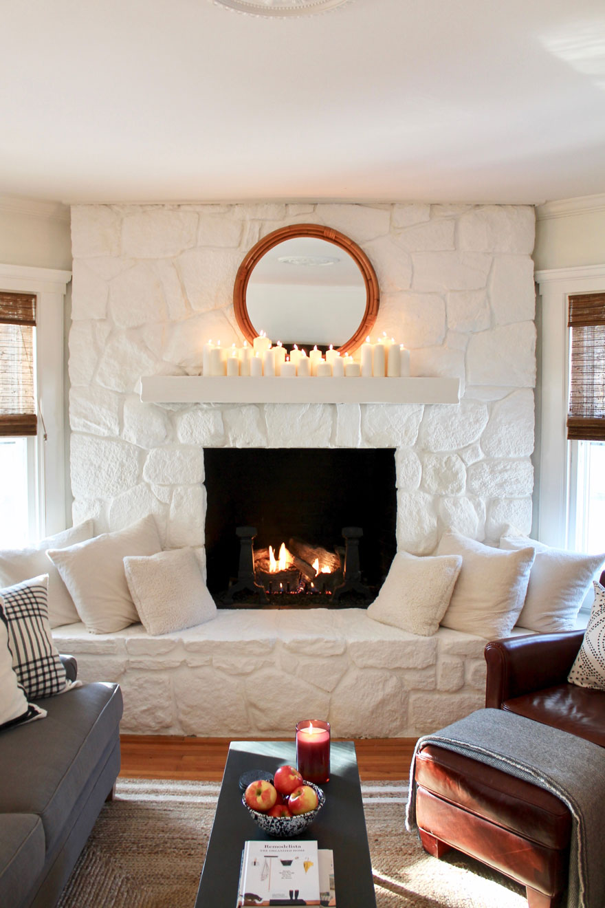 white painted stone fireplace with lots of candles