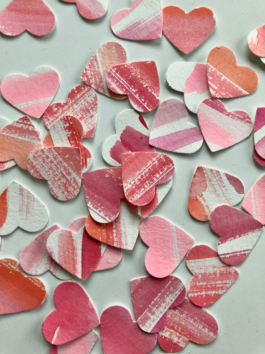 Tiny hearts that look like mini abstract paintings when cut from a paper painted with stripes and using a heart shaped punch