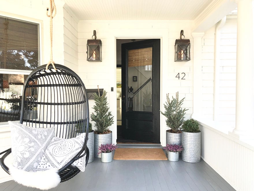 White Cottage front porch with black hanging chair