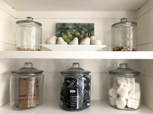 open pantry with glass jars filled with protein bars, nuts, marshmallows