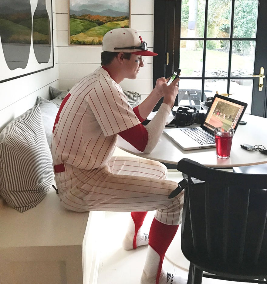 teenage boy in baseball uniform at kitchen table