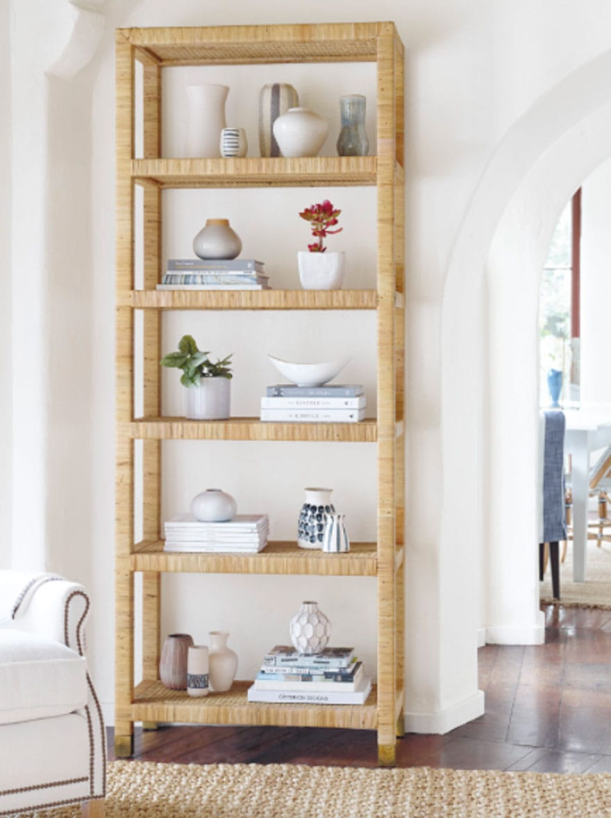 rattan shelf, books, objects on shelf, white walls