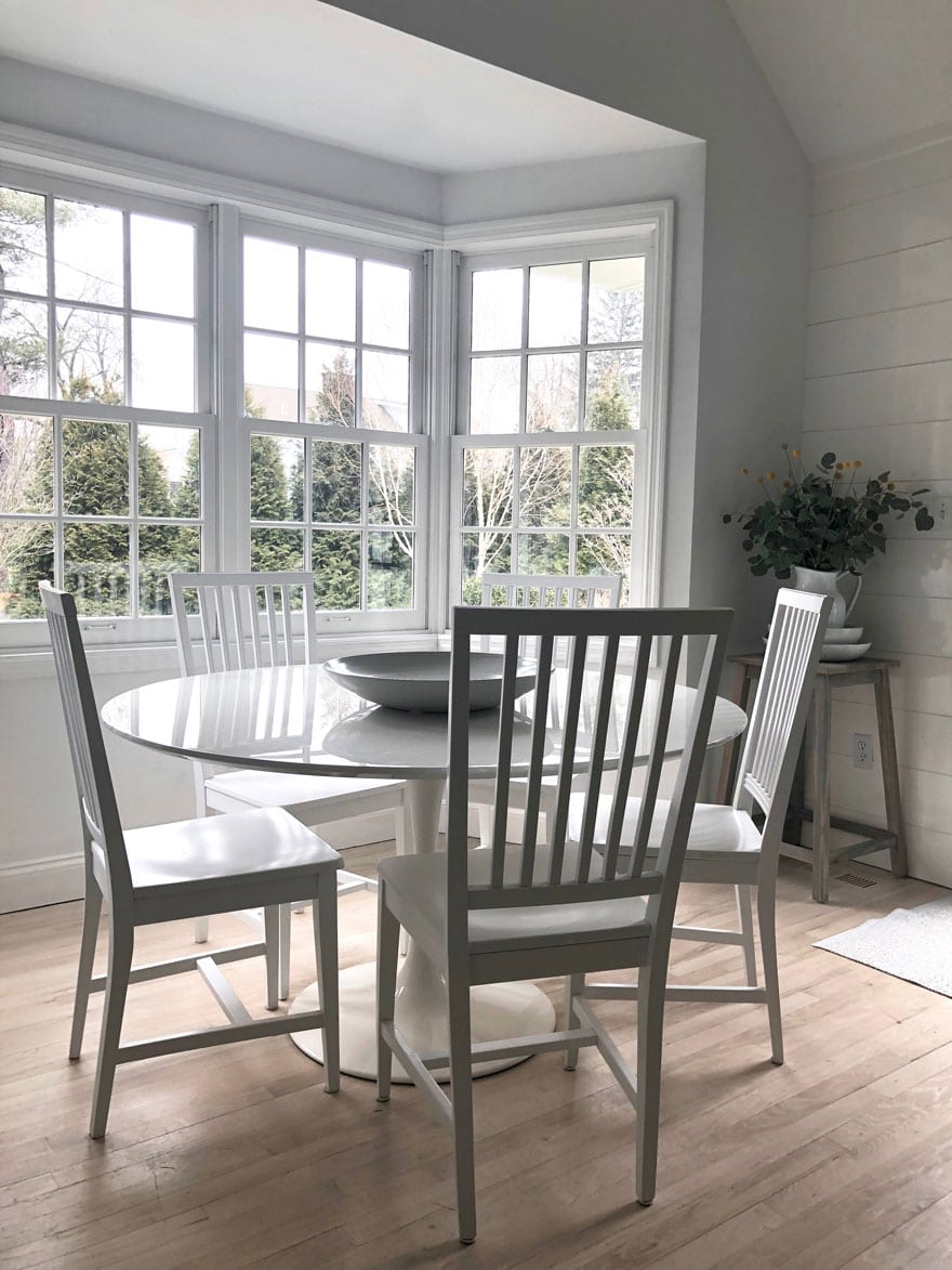 white round table with white chairs in windowed kitchen