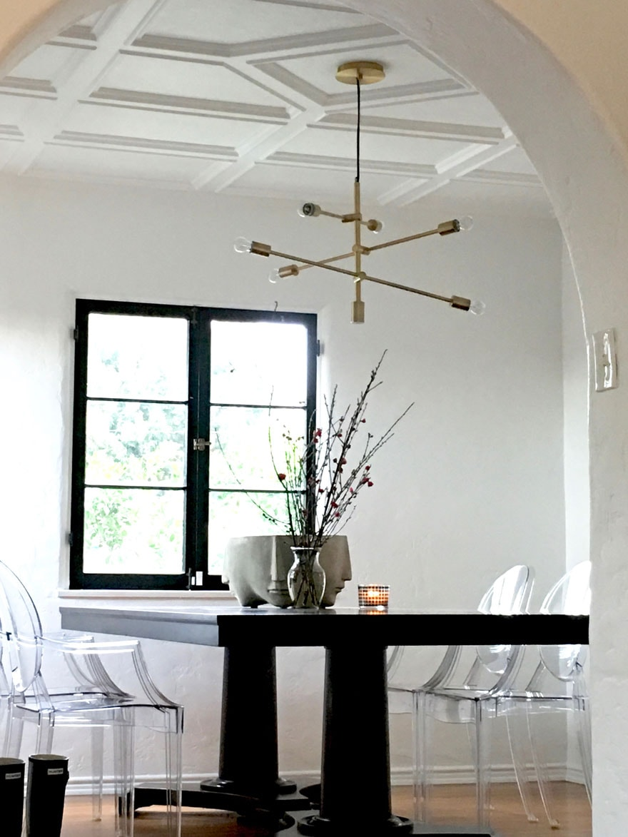 Kartell Ghost chairs in dining room with modern light fixture