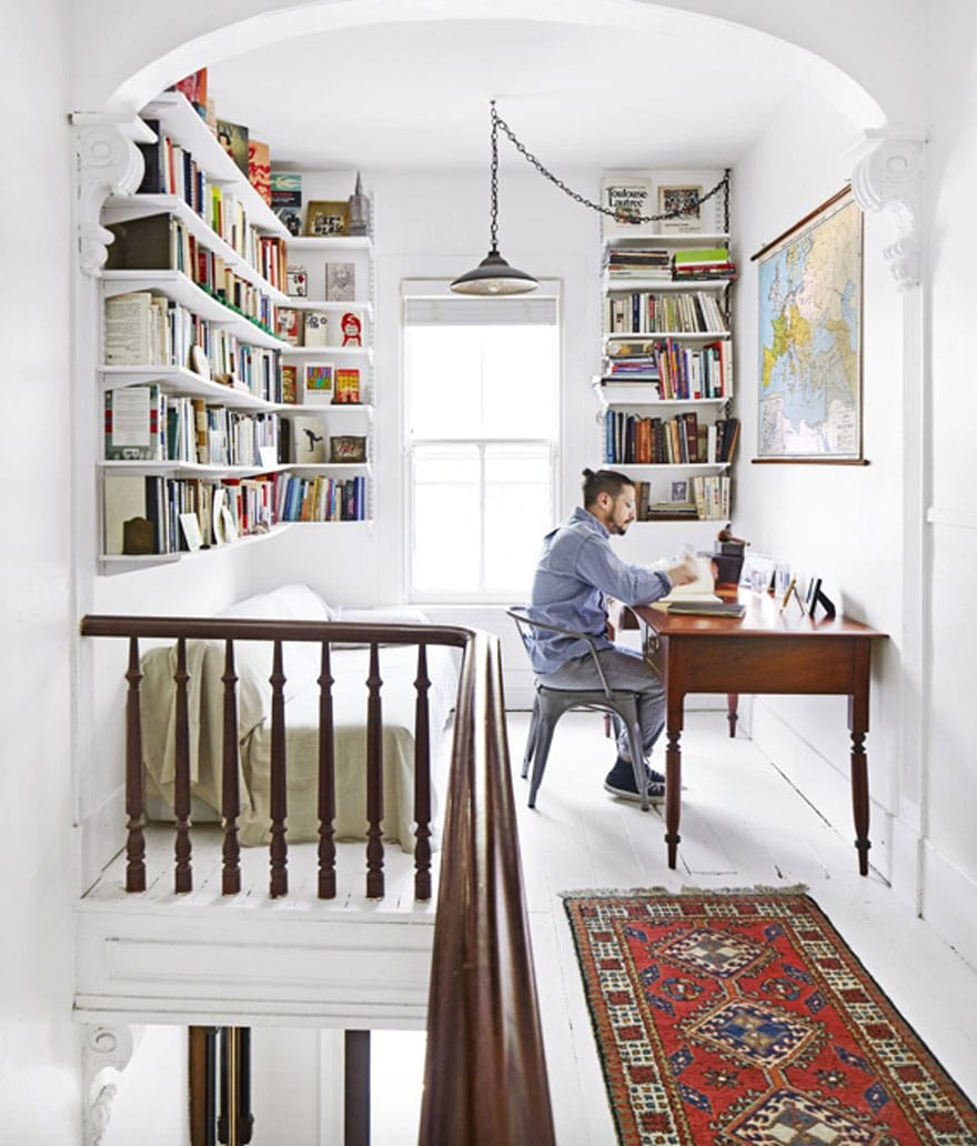 man working at desk in attic office/library