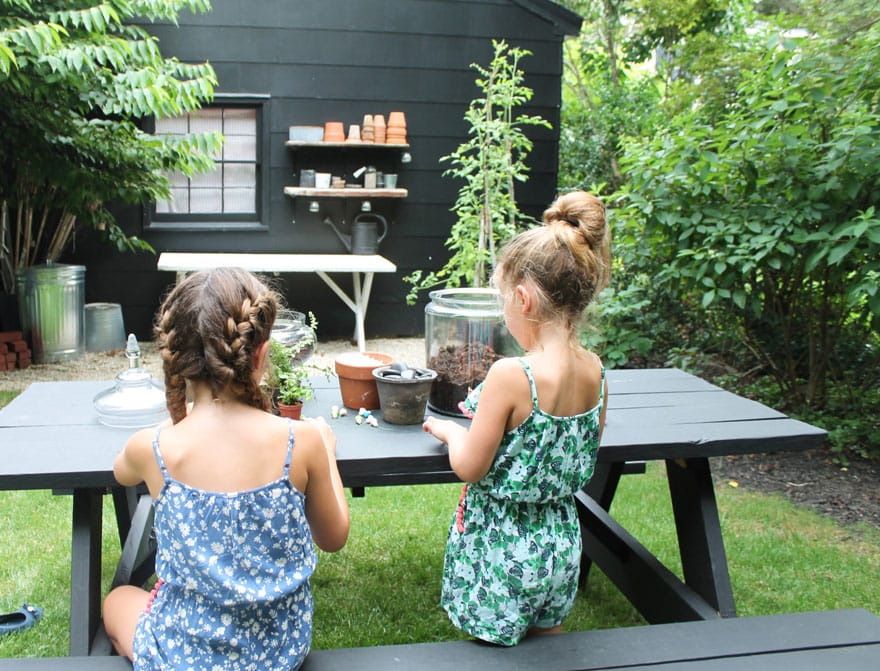 two girls, black garage, table, plants