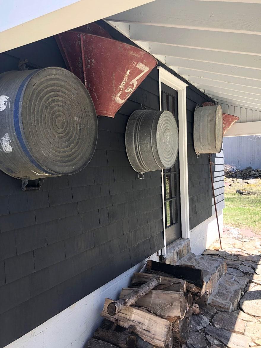 black garage with galvanized buckets on side