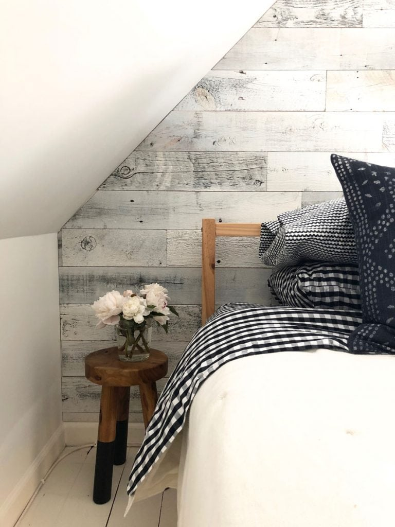 reclaimed wood on walls, stool with peonies next to bed