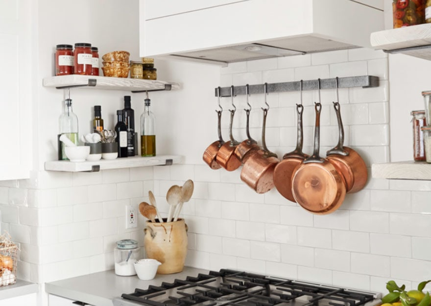 Stove top with copper pots and open shelving in a kitchen