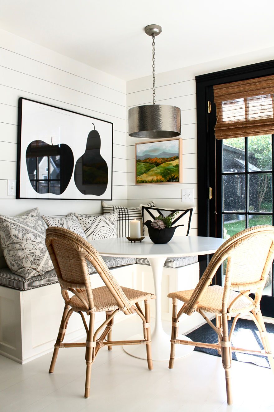 round white table in corner with natural colored chairs with art on wall by sunny windows