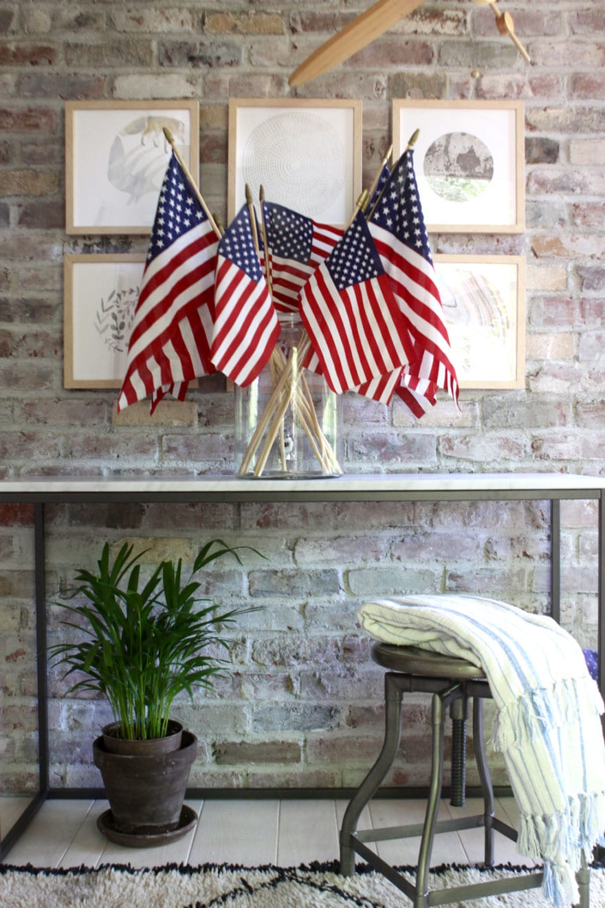 USA flags in clear glass vase against brick wall