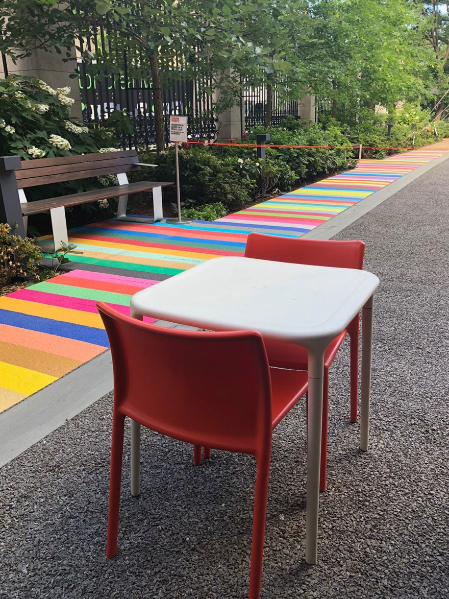 white table and orange chairs outdoor with color walk sidewalk at cooper hewitt Museum