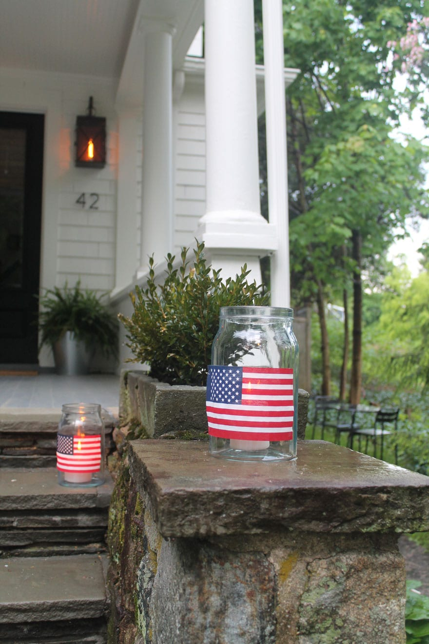 flag with candles inside jar on stone step