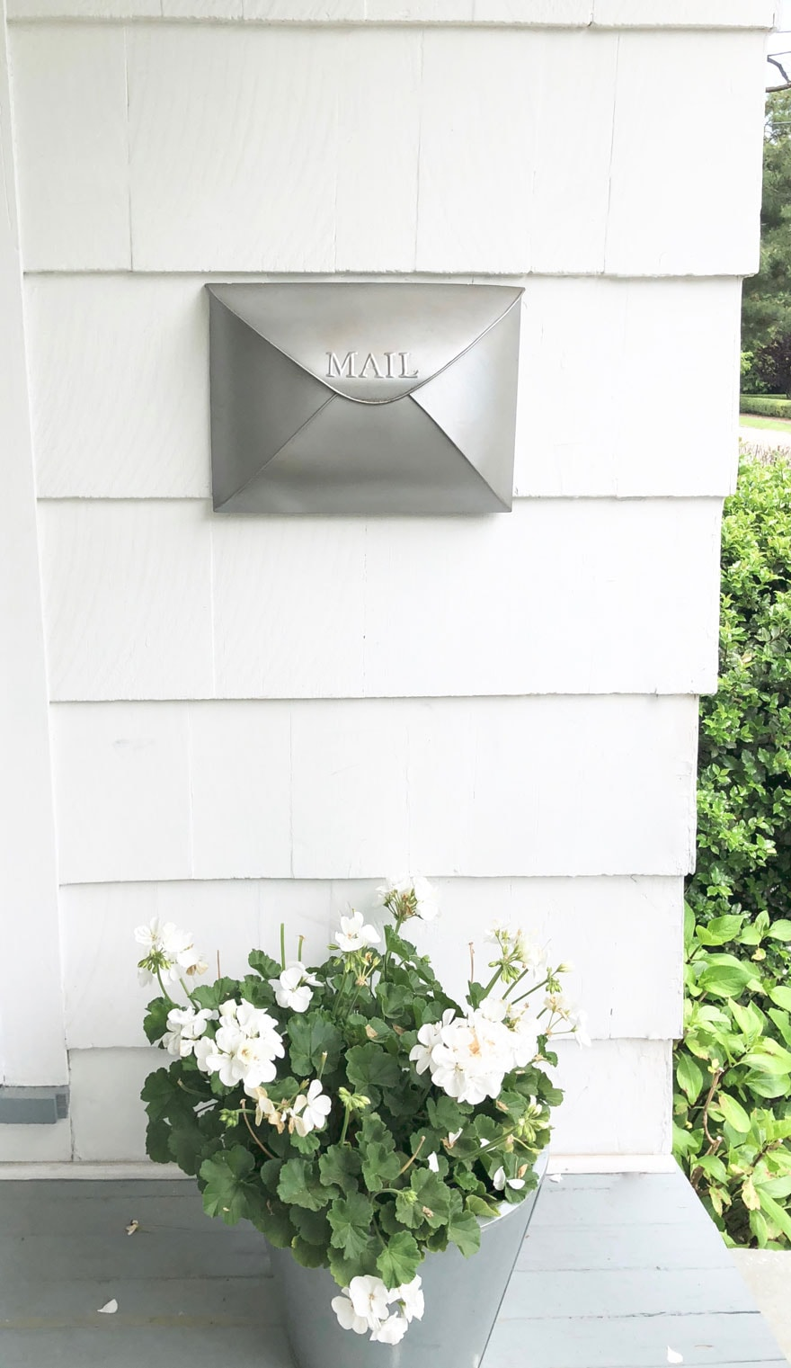 mailbox on white house with geraniums