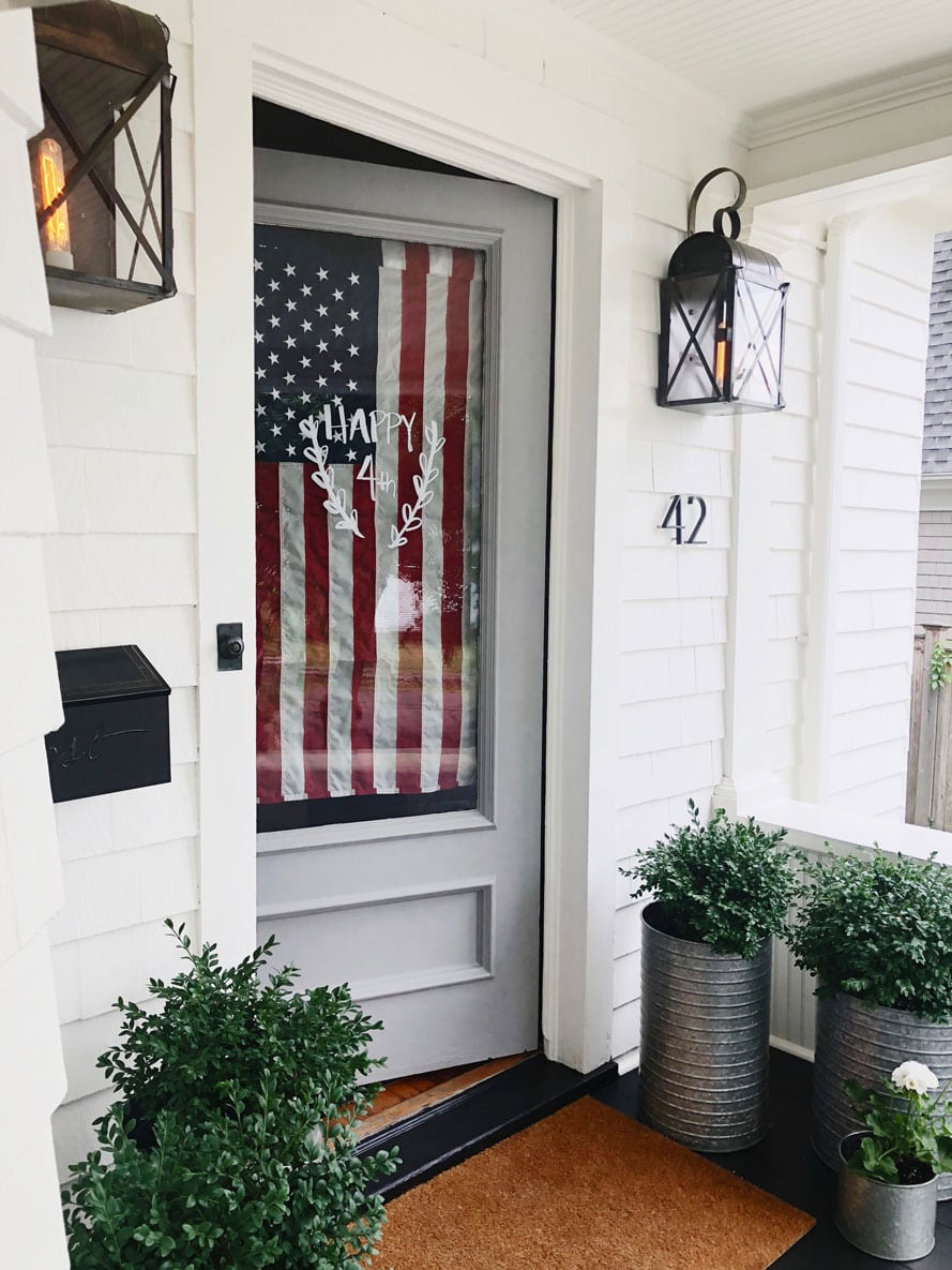 white house with usa flag on glass door, planters