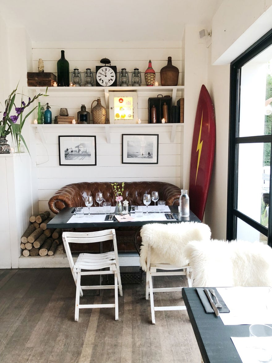 table, sofa, chairs, surf board, bottles