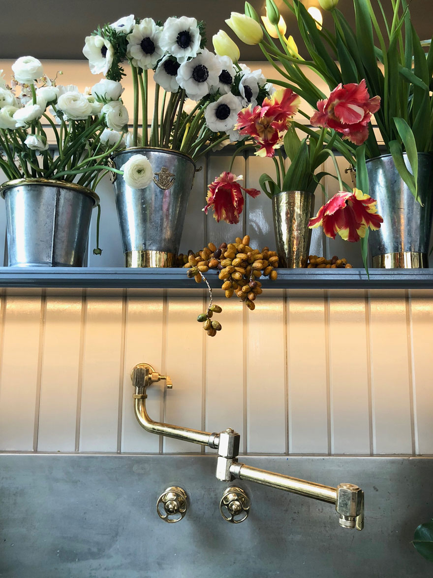 flowers and sink with brass faucet