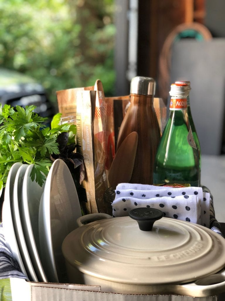 plates, dutch oven, fresh herbs, water bottles, bread in box