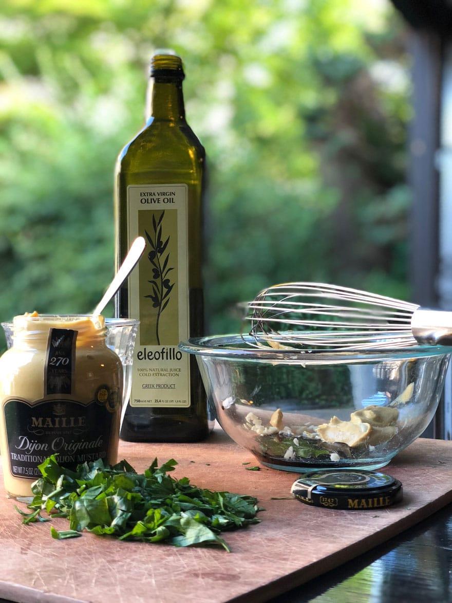 mustard, olive oil, bowl, whisk, fresh herbs