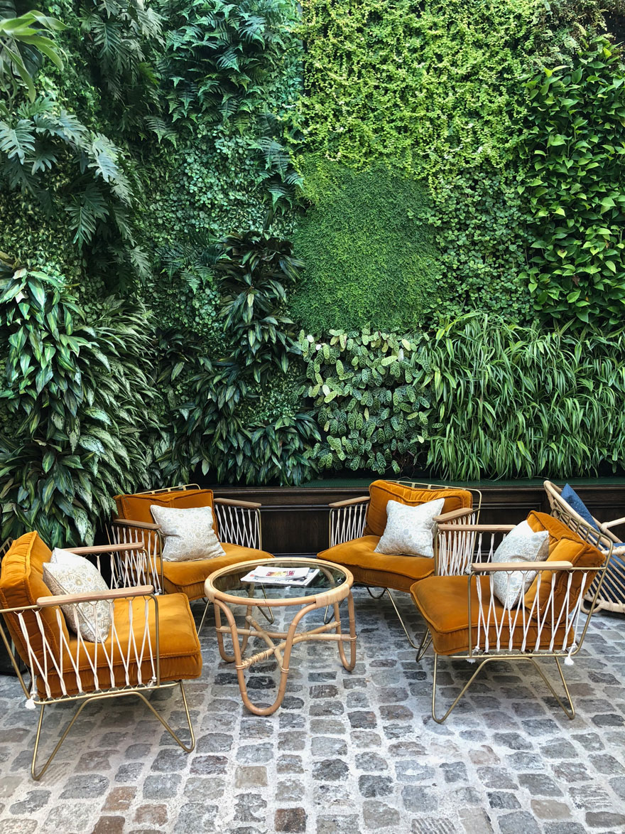 gold chairs against living plant wall