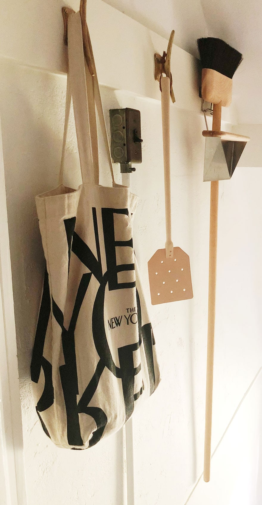tote bag, broom, flyswatter on hooks