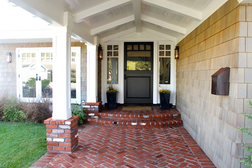 entryway with sconces and herringbone brick walkway