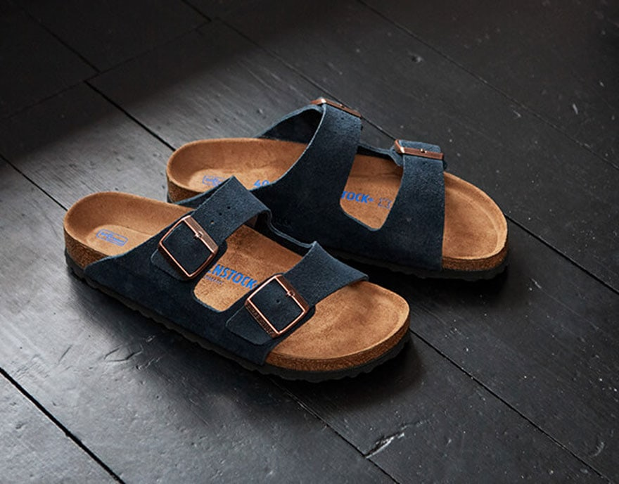 navy suede birkenstocks on black background