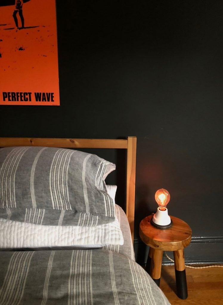bed, black walls, small light