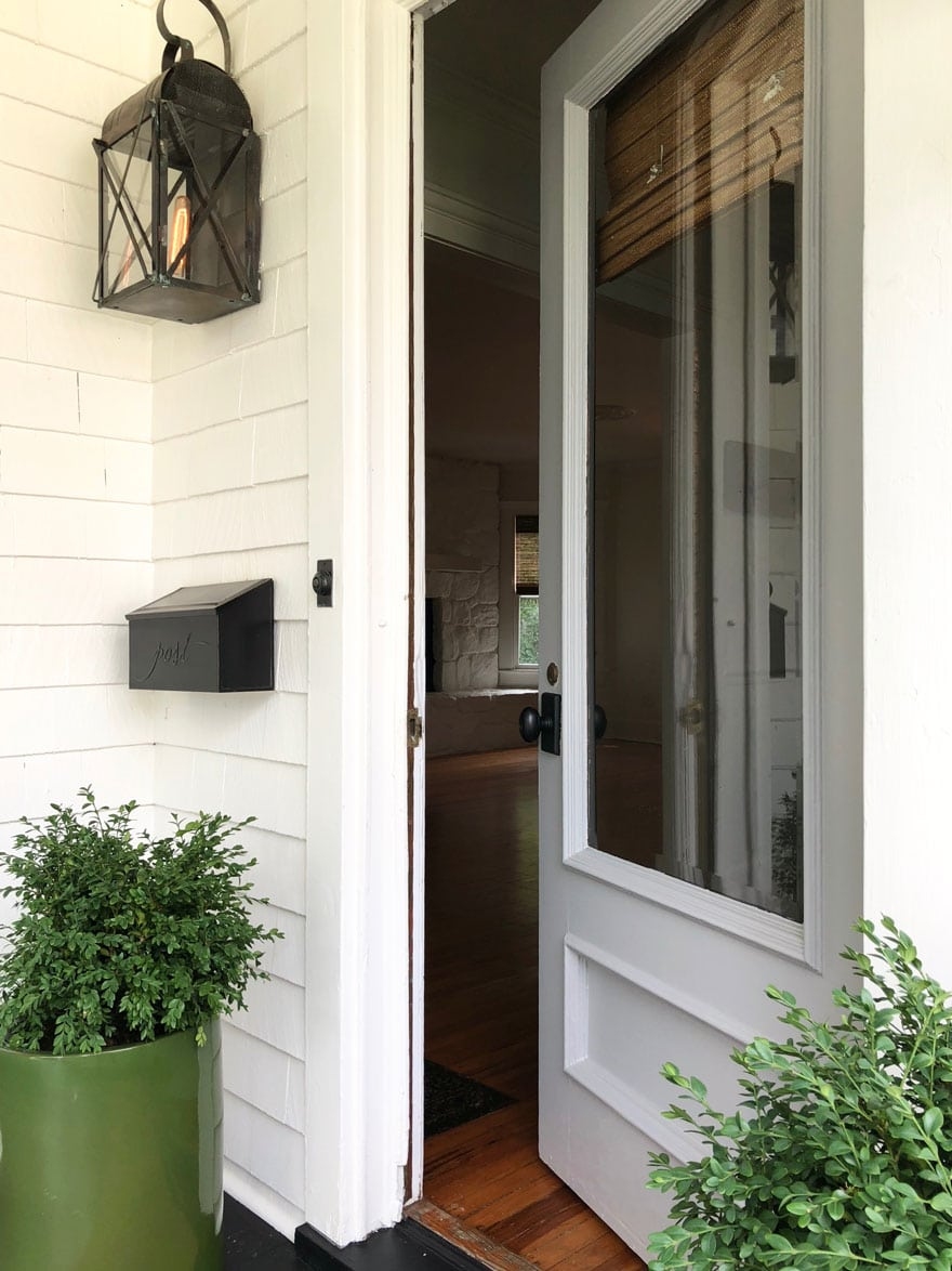 front door with planters and boxwoods, mailbox, white clapboard