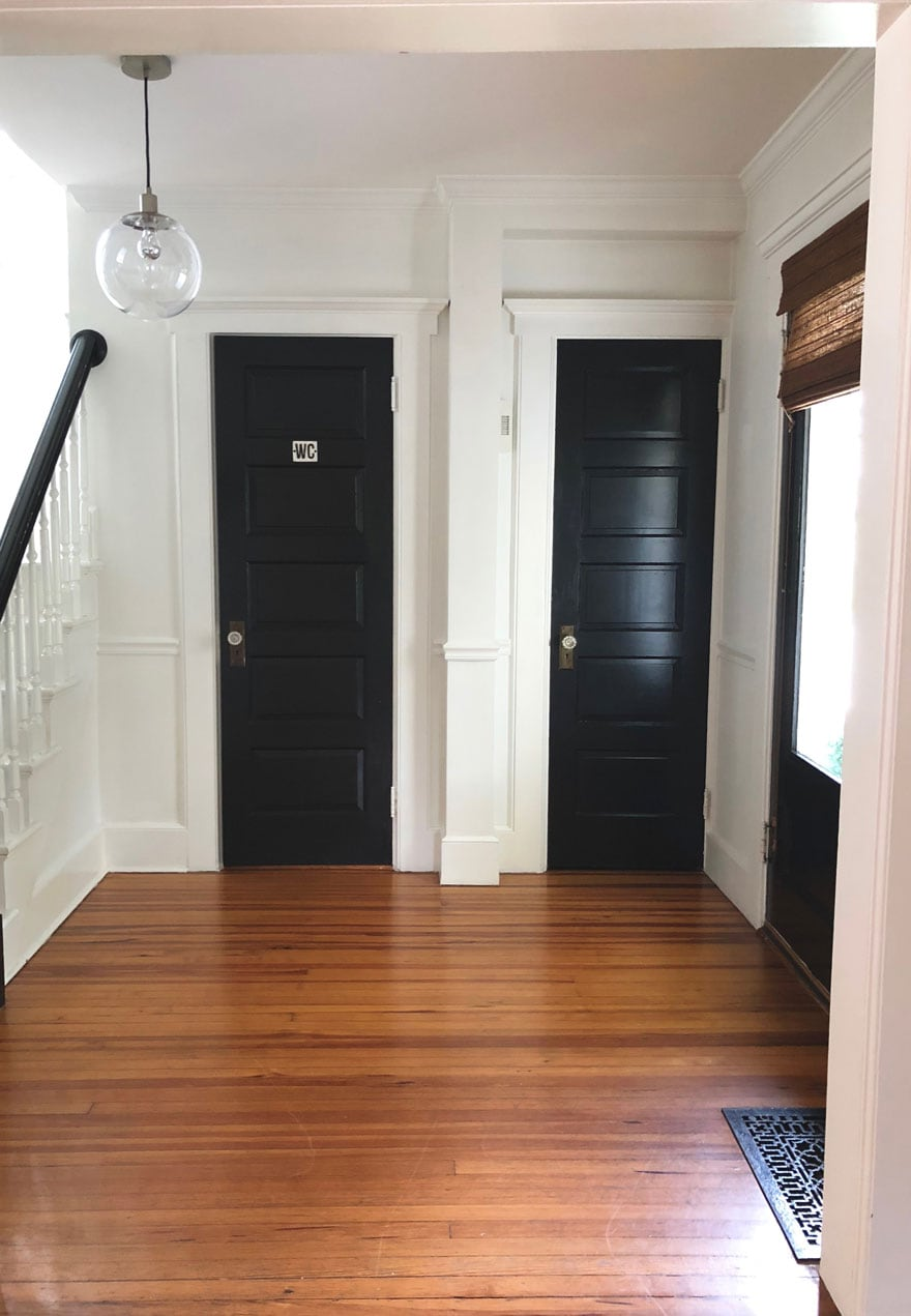 black doors in foyer with wood floors